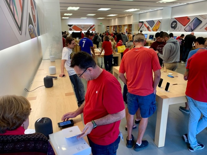 Customers and associates in a busy Apple retail store.