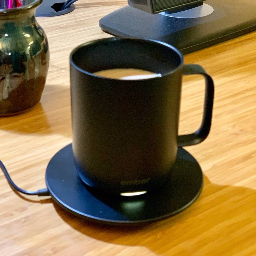 Ember Mug sitting on charging coaster on a desk.